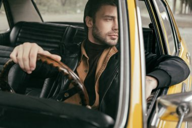 pensive handsome stylish man sitting in retro car and looking away