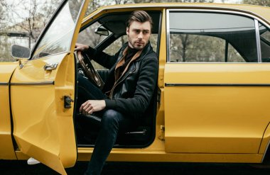 handsome stylish young man in leather jacket sitting in yellow classic car and looking away