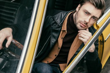 pensive handsome young man sitting in classic car and looking at camera