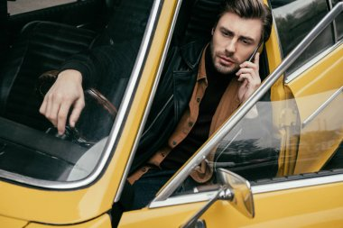 handsome stylish man talking by smartphone while sitting in yellow classic car