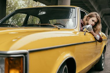 attractive young woman looking at camera while sitting in yellow vintage car