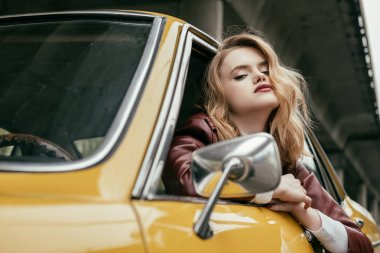seductive girl in leather jacket looking at camera while sitting in yellow retro car