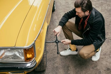 high angle view of handsome man in leather jacket fixing wheel of yellow vintage car