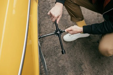cropped shot of man in leather jacket fixing wheel of yellow vintage car