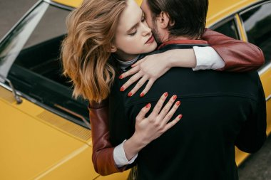 high angle view of stylish young couple hugging near yellow car