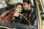Fotografie beautiful smiling young couple in leather jackets sitting together in classic car
