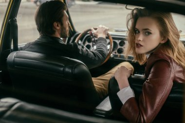 stylish girl looking at camera while sitting in car with handsome boyfriend