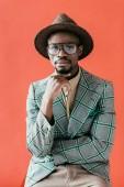 Američan Afričana muž v módní brýle a klobouk pózuje pro vintage módní střílet, izolované na červené