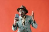 Fotografie Šokovaný afroamerické muže pomocí smartphone, izolované na červené