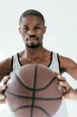Fotografie Selektivní fokus americký basketbalista držení míče, izolované na bílém