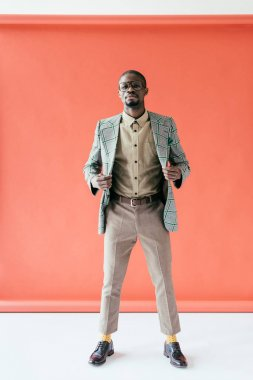 fashionable african american man in eyeglasses and retro jacket posing on red