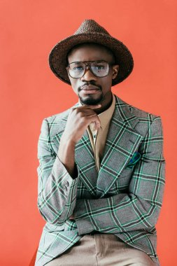 african american man in trendy eyeglasses and hat posing for vintage fashion shoot, isolated on red