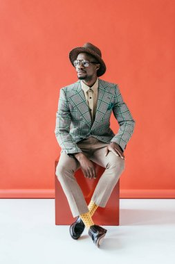 stylish african american man posing in retro hat, on red