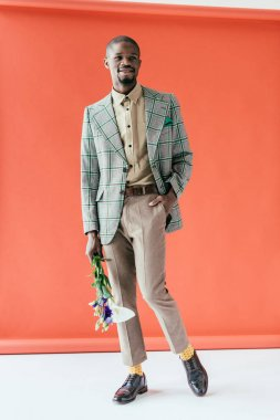 fashionable african american man in retro jacket with flowers, on red