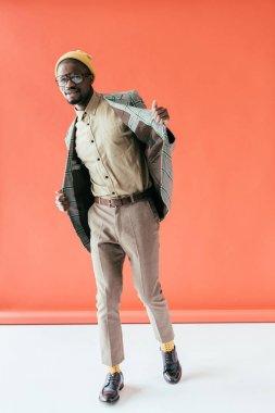 african american man in trendy vintage jacket, on red