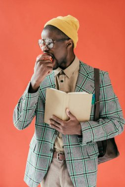 handsome african american man with book eating apple, isolated on red