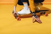 Tiefschnitt-Ansicht des Skateboarders in weißen Turnschuhen auf Longboard, auf gelb