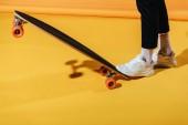 abgeschnittene Ansicht eines stylischen Mannes in weißen Turnschuhen mit Longboard, auf gelb