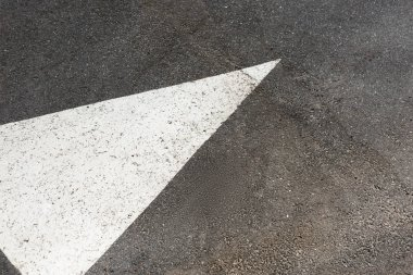 White painted arrow on asphalt road