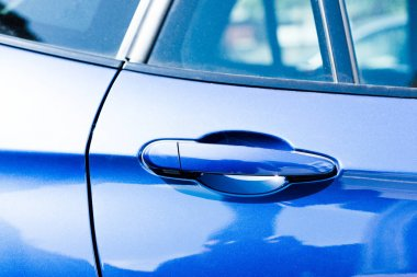 Close-up view of handle in blue car door