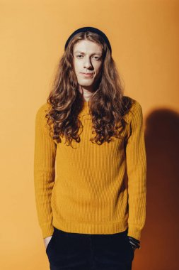 handsome fashionable man with long hair looking at camera, on yellow