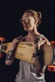 Fotografia moda uomo tatuato che tiene longboard, isolato sul nero