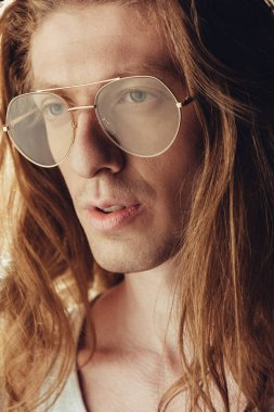 portrait of fashionable man with long hair in stylish eyeglasses, on black