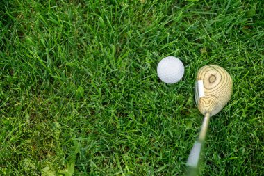 top view of golf club and ball on green grass