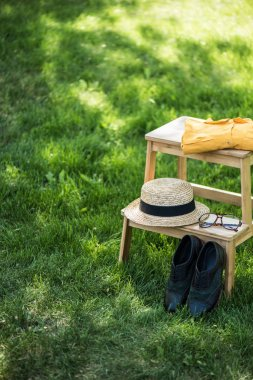 close up view of arrangement of eyeglasses, black shoes, shirt and hat on wooden stairs on green grass