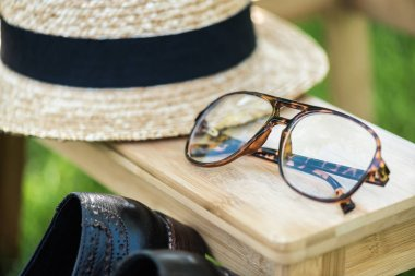 close up view of arrangement of eyeglasses, black shoes and hat on wooden stairs on green grass