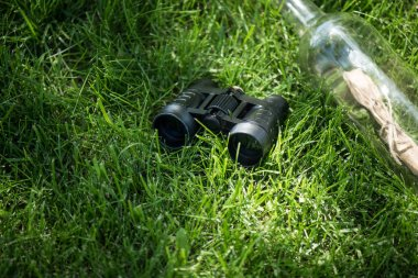 close up view of binoculars and paper in glass bottle arranged on green lawn