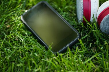 close up view of smartphone with  blank screen and headphones on green grass
