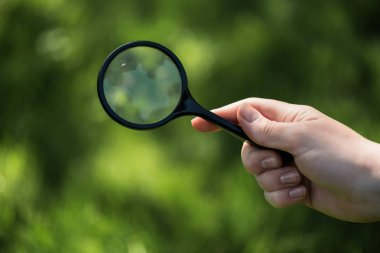 partial view of woman with magnifying glass in hand on green blurred backdrop