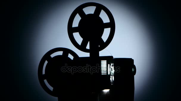Old projector turns the tape. Dark silhouette studio
