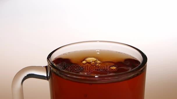 Kus cukru spadá do šálku čaje. Close ups