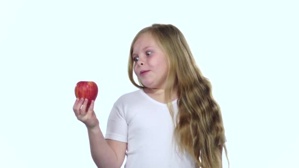 Little girl is holding an apple and sniffing it, it smells delicious. White background. Slow motion