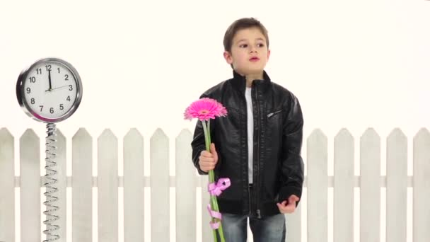 Little guy is standing and waiting for his girlfriend with flowers, she does not come. White background. Slow motion