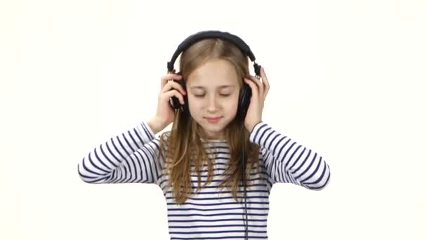Child puts on headphones and starts dance to music, studio