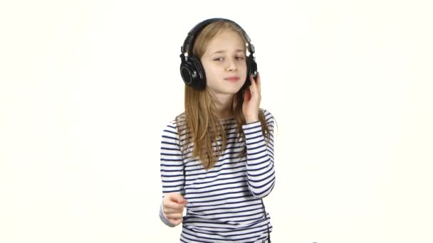 Child listens music in headphones and snaps fingers into rhythm