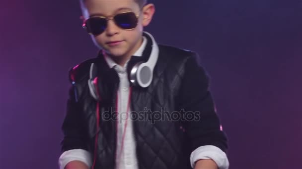 Stylish boy in glasses mixes music, colorful smoke. Slow motion