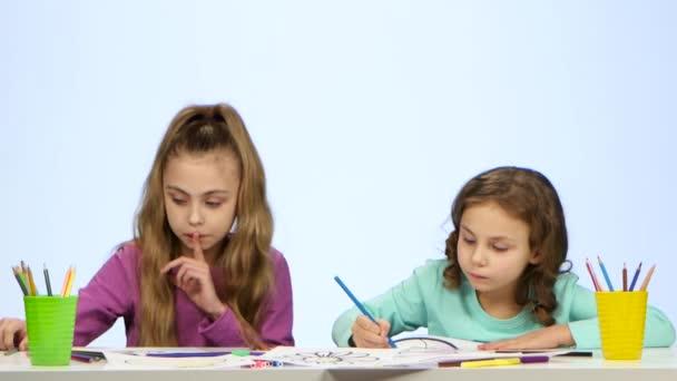 Sestry děti zdobí obrázek s tužky. Bílé pozadí
