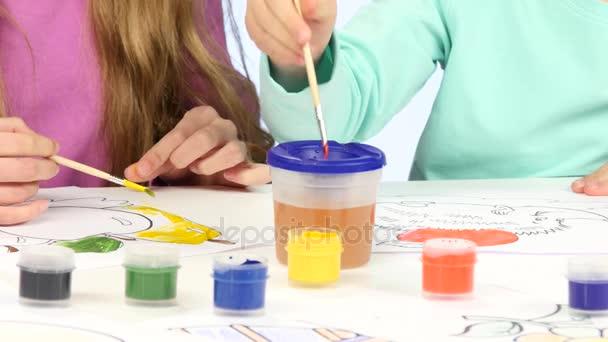 Malé děti s pomocí štětce a barvy zdobí kresby, se jim to líbí. Zblízka. Bílé pozadí