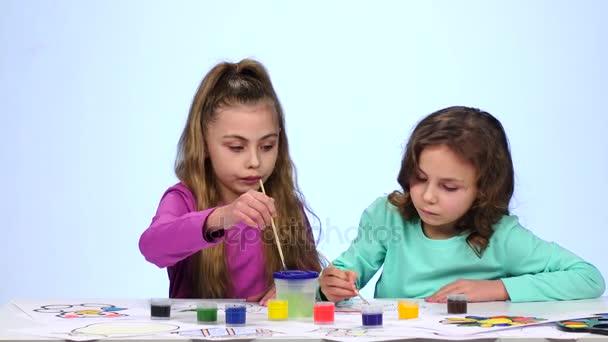 Děti vybarví obrázek, dabs štětcem ve sklenici s vodou. Zblízka. Bílé pozadí. Časová prodleva