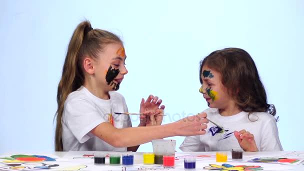 A gyerek ül az asztalnál, festékek alkalmazása a ruhájuk. Fehér háttér. Lassú mozgás