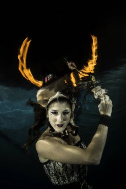 Girl underwater with fire look like a horn