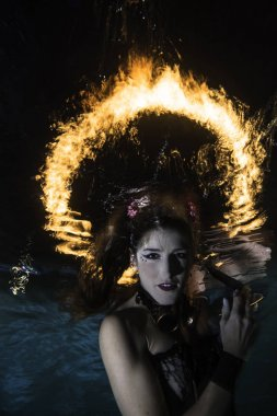 Woman underwater posing with a ring of fire in the background
