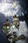 Photo A tattooed chef posing with vegetables underwater