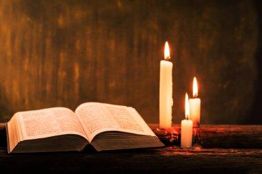 İncil haç ve boncuk eski meşe ahşap bir masa üzerinde bir mum. Güzel altın arka plan. Din kavramı.