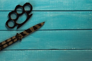 Steel butterfly knife and Brass knuckles on a beautiful blue wooden background.