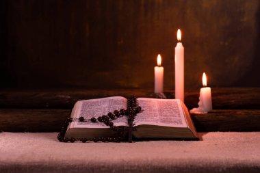 İncil ve eski meşe ahşap bir masa üzerine de mum. Güzel altın arka plan. Din kavramı.